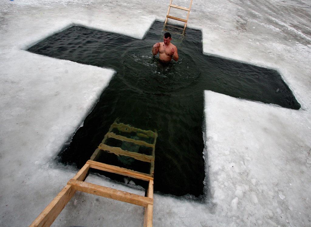 예수세례 축일에 러시아인이 얼음 물 속에 몸을 담그고 있다.