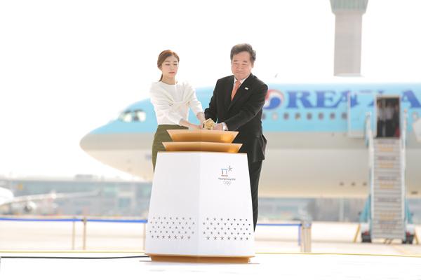김연아와 이낙연 총리가 지난해 11월 1일 그리스에서 채화된 평창 동계올림픽 성화에 불을 붙이고 있다.
