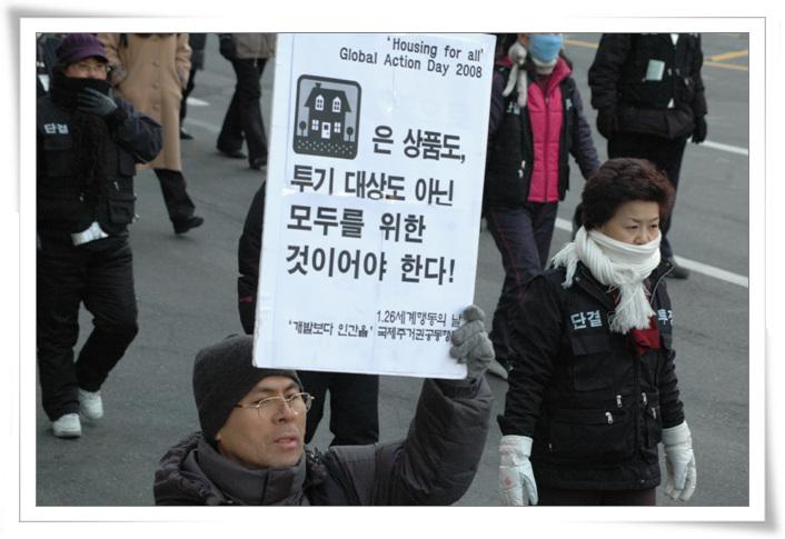 2008년 1월 26일 주거권공동행동 행진 모습. 피켓을 들고 있는 사람은 용산참사 생존자 김재호 씨다. 역시 공동정점으로 수감되어 있는 동안 딸에게 보내는 편지를 만화로 그려 <꽃피는 용산>이라는 책을 출간하기도 했다. 오른쪽에 있는 사람은 용산참사 이후 용산4구역 현장 투쟁 당시 위원장을 했던 노안나 씨다. 이 참사의 피해자 범주에는 많은 사람들이 포함된다.