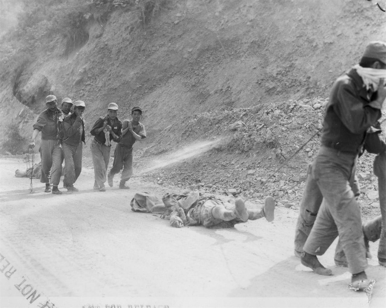 1951. 5. 24. 중국군 시신을 매장하고자 밧줄로 끌어 옮기고 있다.