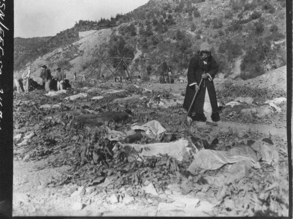 1950. 11. 14. 함흥. 어느 아버지가 덕산 광산 인근 밭에 늘려져 있는 400여 구의 학살 시신 가운데서 아들을 찾고 있다.