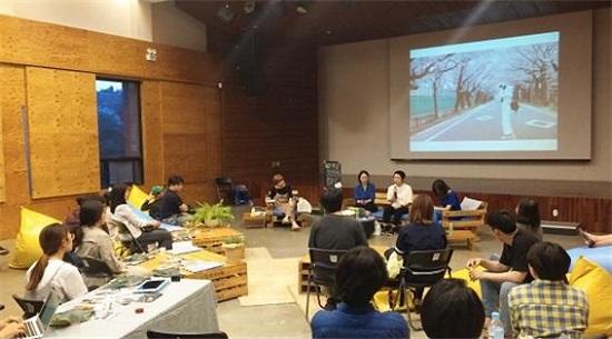 무스부의 미야모토 대표(스크린 앞 흰옷)가 후쿠시마의 요노모리에 방호복을 입고 들어가 찍은 사진에 대해 설명하고 있다. 활동가와 일반 시민 등 40여 명의 청중은 자유롭게 배치된 자리에 앉아 '후쿠시마 이후의 삶'에 대해 열심히 묻고 공감했다.