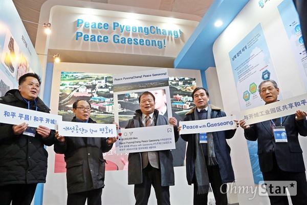 """개성공단기업협회가 5일 '평창2018페스티벌파크'에 개성공단 홍보관(Peace Pyeongchang! Peace Gaeseong!)을 열었다. 신한용 회장(가운데)을 비롯한 개성공단 입주기업 관계자들이 개성공단 재개를 원하는 마음을 담아 피켓을 든 채 """"개성공단 가고 싶다""""라고 외치고 있다."""