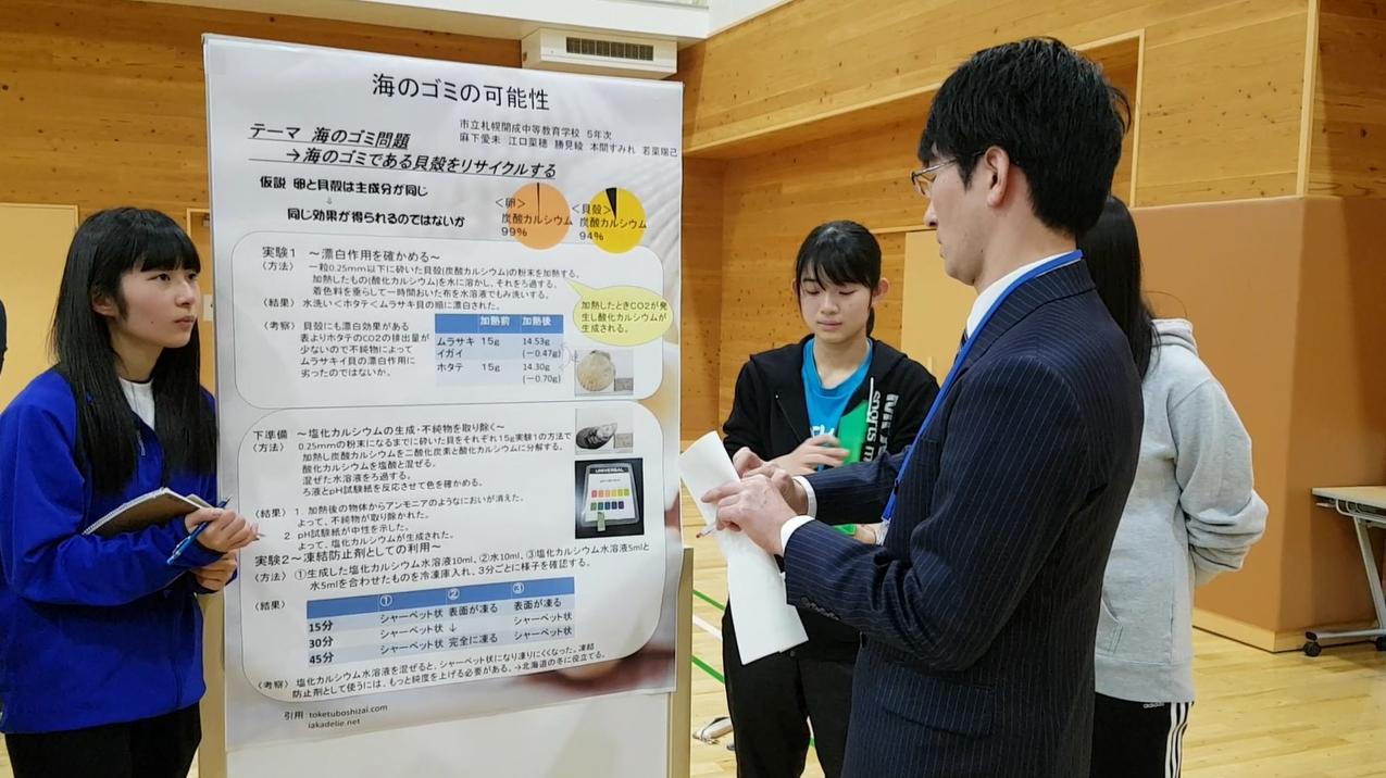 삿포로 가이세이 중등교육학교의 소논문 포스터 발표 행사에서 지도 교사(오른쪽)가 학생들에게 도움말을 해 주고 있다.
