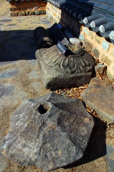 진주 묘엄사지 3층 석탑 주위에 있는  주춧돌과 석주, 부도의 덮개돌로 추정된 팔각형의 석재.