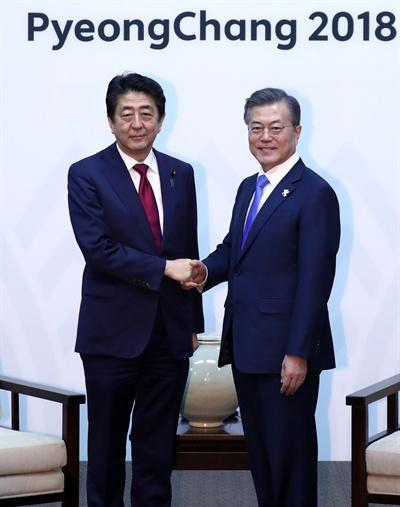 문재인 대통령이 평창올림픽 개막식이 열리는 9일 오후 강원도 용평 블리스힐스테이에서 아베 신조 일본 총리와 만나 악수하고 있다.