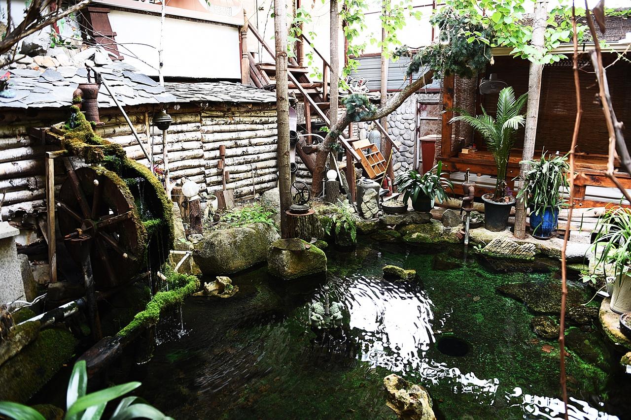 진미식당 내부 식당에 들어가면 작은 연못과 물레방아가 있다. 이 연못을 보는 자리가 가장 먼저 들어찬다.