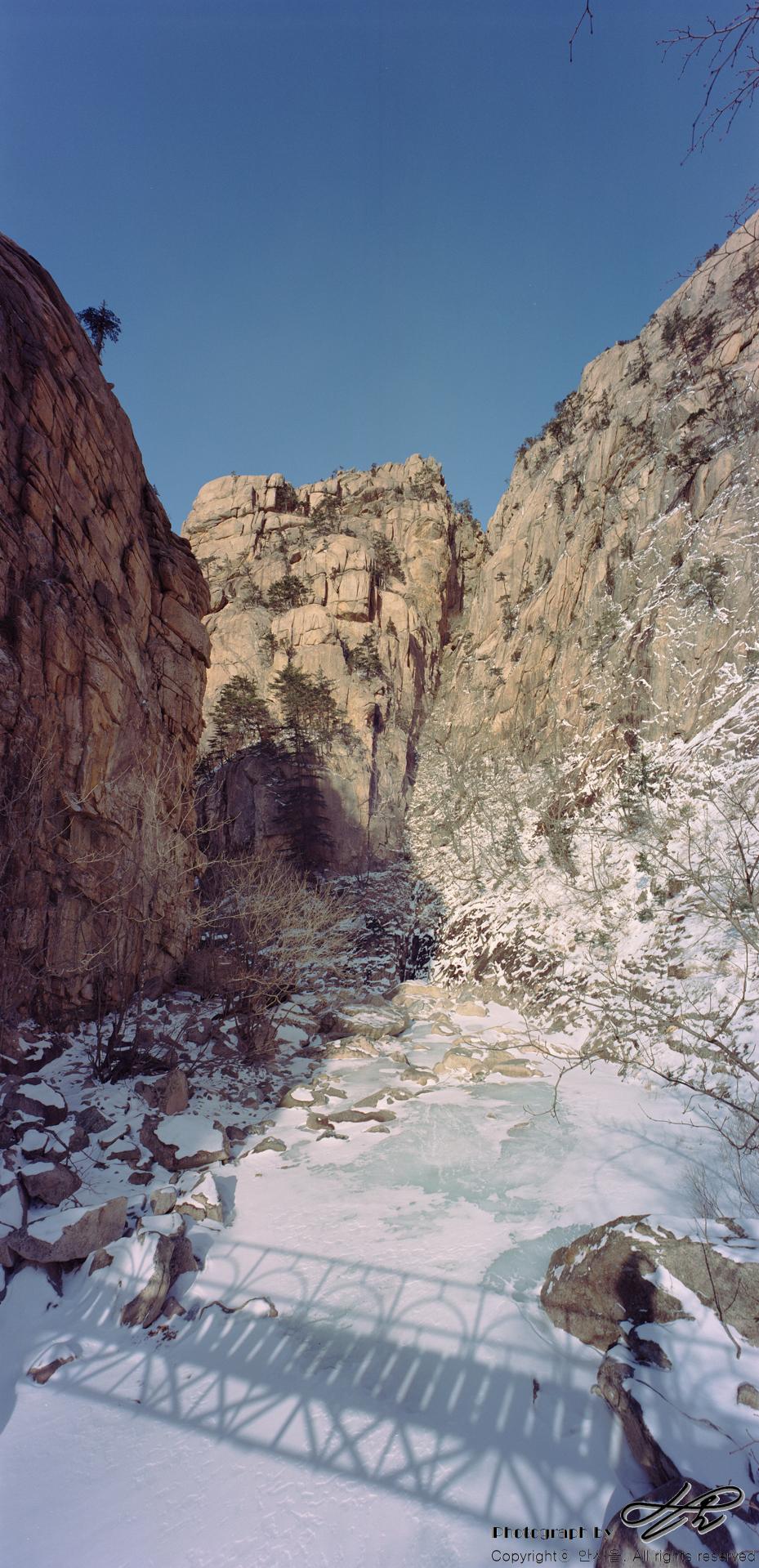 천불동계곡 얼어붙은 천불동계곡 위로 눈이 얇게 쌓여있고 철다리의 그림자가 드리워 있다.