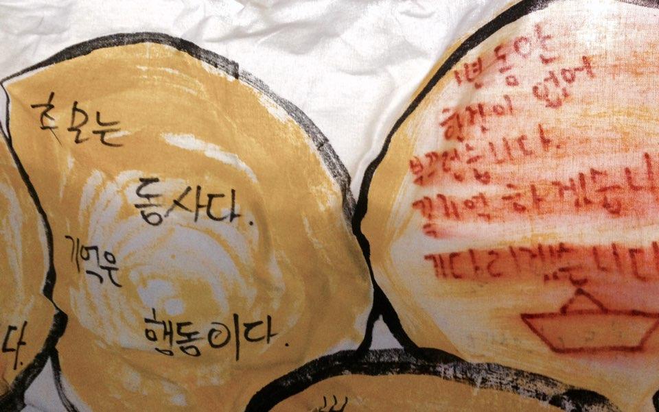 현수막에 새겨진 글귀 '추모는 동사다, 기억은 행동이다' , '1년 동안 한 것이 없어 부끄럽습니다. 꼭 기억하겠습니다, 기다리겠습니다' 라고 적혀 있다.