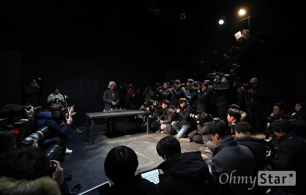 """""""이윤택, 사죄는 당사자에게 하라"""" 이윤택 전 연희단거리패 예술감독이 19일 오전 서울 종로구 30스튜디오에서 성추행 사실에 대한 사과 기자회견을 하고 있는 동안 한 연극배우가 항의피켓을 들고 있다."""