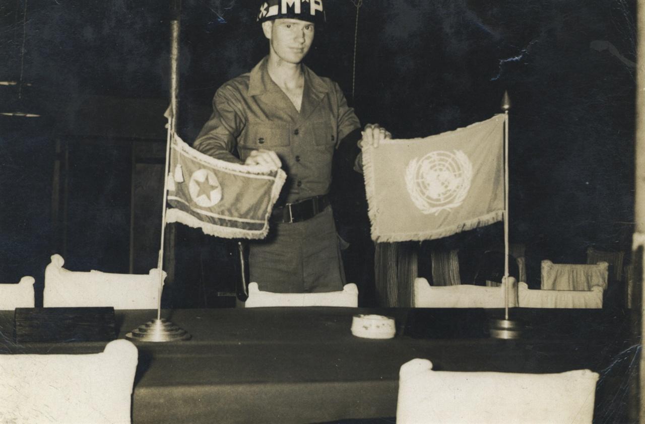 판문점 정전회담장소에서 UN 깃발과 북한 인공기를 올려놓은 테이블 뒤에서 깃발들을 잡고 서있는 미국 M P.