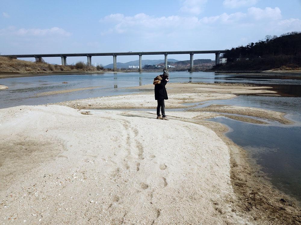 대전·당진 간 고속도로 밑 드러난 모래톱에서 이용희 활동가가 사진을 찍고 있다.