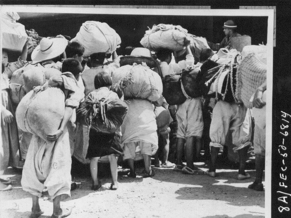 1950. 8. 23. 경남 함안, 가재도구를 이고 진 피란민들이 열차표를 사려고 몰려들자 든 미 헌병이 이들을 통제하고 있다.