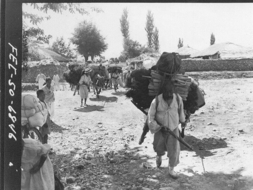 1950. 8. 24. 낙동강 유역. 가재도구를 머리에 이고 등에 진 피란민 행렬.