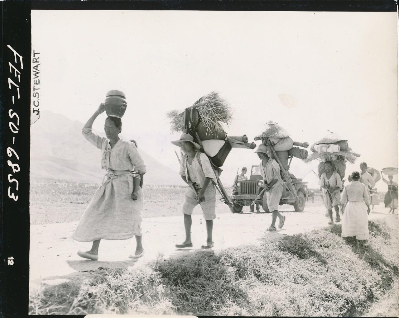 1950. 8. 24. 낙동강 유역. 유엔군의 통제 속에 가재도구를 머리에 이고 진 피란민들의 행렬.