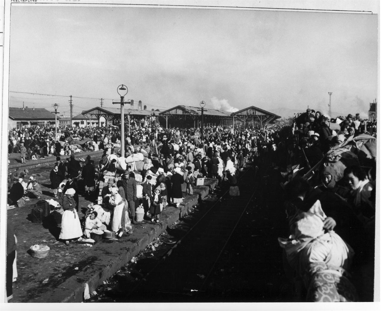 1951. 1. 3. 인천, 인천시민들이 플랫폼을 가득 메운 채 피란열차를 기다리고 있다. 선로 위 무개화차에도 피란민들로 가득 찼다.