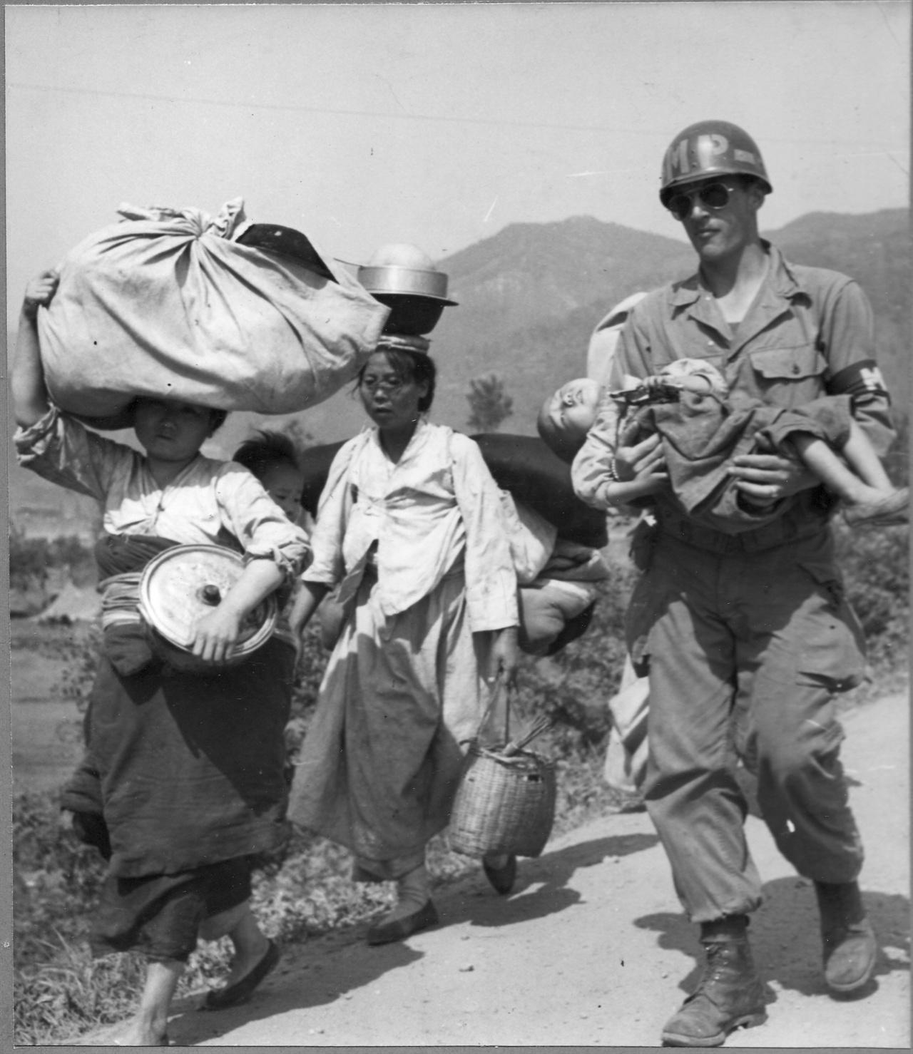 화천, 한 유엔군이 아이를 안아 피란길을 도와주고 있다.