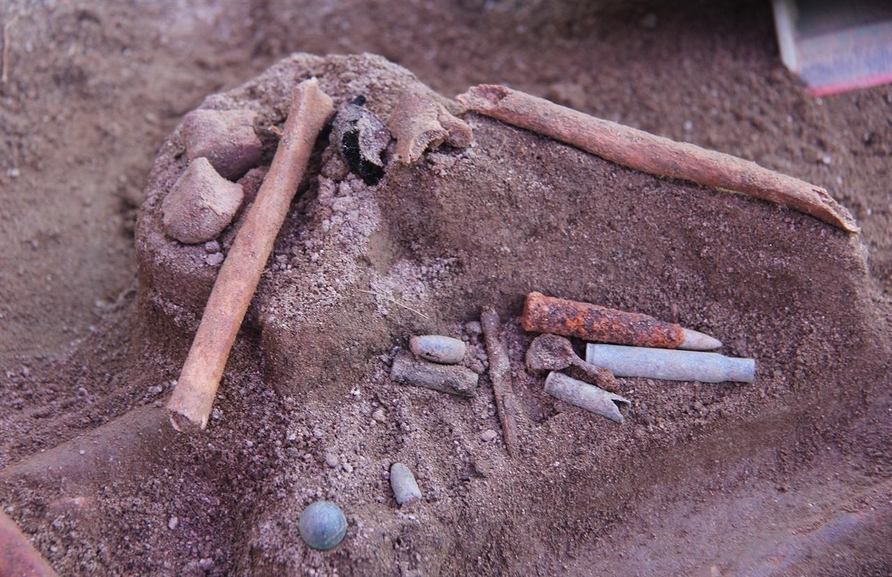 8~9세 아이의 정강이뼈 아래에서 아이의 것으로 보이는 구슬이 발견됐다. 아이 유해 위에서는 다량의 탄티와 탄두가 나왔다. 아이 유해 아래 아이의 엄마로 보이는 유해가 뒤엉켜 있다.