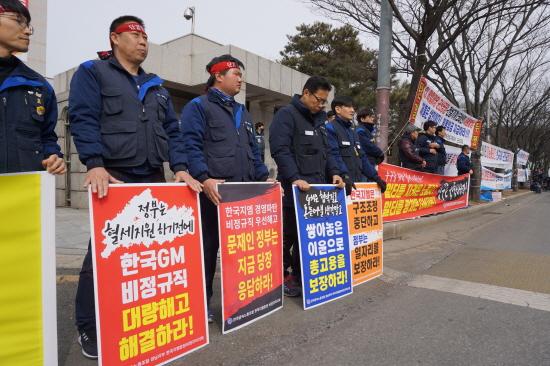 한국GM 비정규직지회 노동자들이 27일 군산시청 앞에서 열린 결의대회에서 피켓을 들고 참석했다.
