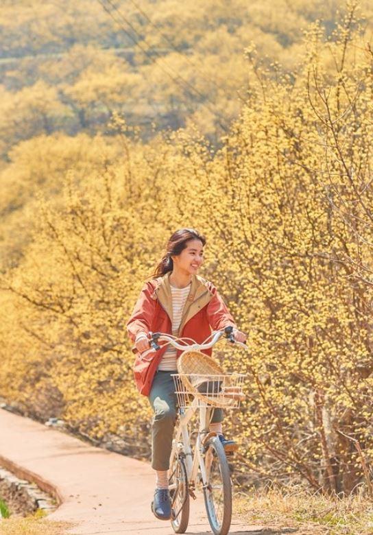 배우 김태리가 의성 산수유마을에서 자전거를 타고 있다.