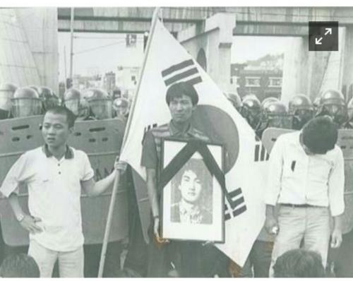 1987년에 경찰이 쏜 최루탄에 머리를 맞아 숨진 연세대 학생 고 이한열열사의 장례식 사진 1987년 이한열 열사의 영정사진을 들고있는 가운데 학생이 당시 연세대 총학생회장이었던 우상호 의원이다. 좌측에 배우 우현과 함께