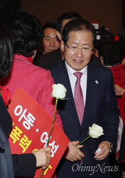 '미투' 상징 흰 장미 든 홍준표 자유한국당 홍준표 대표가 6일 오후 서울 여의도 중소기업중앙회 그랜드홀에서 열린 제1차 자유한국당 전국여성대회에 입장하며 미투 운동을 상징하는 흰 장미를 받아들고 있다.