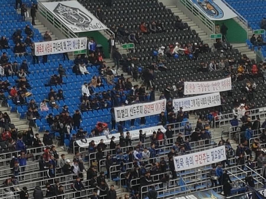 """인천 유나이티드 서포터스가 경기 시작 전 개막 행사 순간 관중석 곳곳에서 """"침묵 속의 구단주는 필요없다"""" 등의 플래카드를 펼쳤다."""