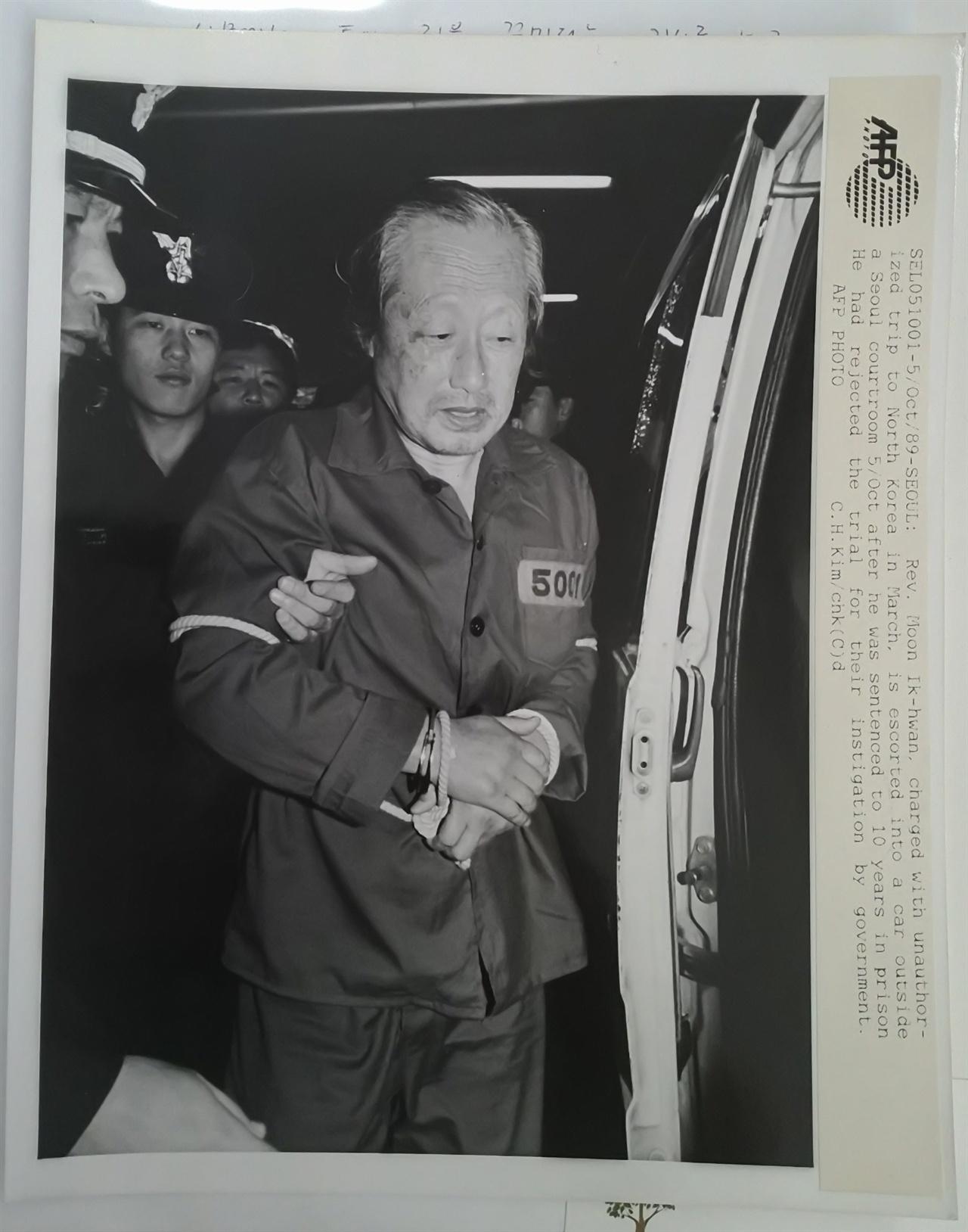호송되는 문익환 오랏줄에 묶인 통일염원, 방북 재판에서 10년형이 선고된 문익환이 호송차량으로 이동하고 있다. 경찰은 기자들의 눈을 피해 이송했고, 이를 AFP통신 김철한 기자가 단독으로 포착했다(기증사진).