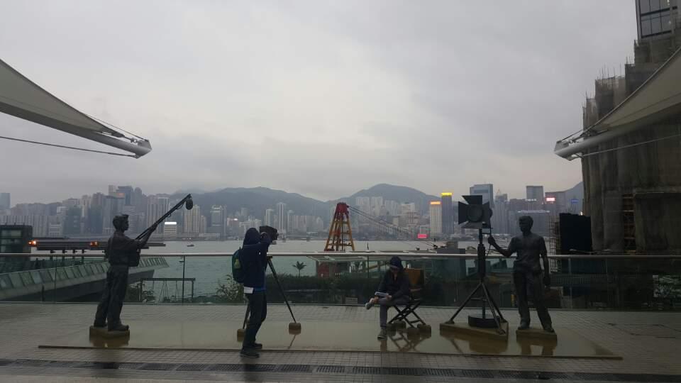 영화 촬영 장면을 형상화한 조형물과 전경으로 보이는 홍콩섬.