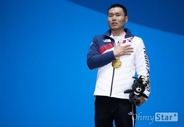 노르딕스키 신의현 선수가 17일 오후 강원도 평창 올림픽메달플라자에서 열린 크로스컨트리 남자 7.5km 좌식 부문 수상식에서 수상한 금메달을 메고 애국가 연주에 맞춰 국기에 대한 경례를 하고 있다. 신 선수는 22분 28초 40으로 1위를 기록해 금메달을 따냈다.