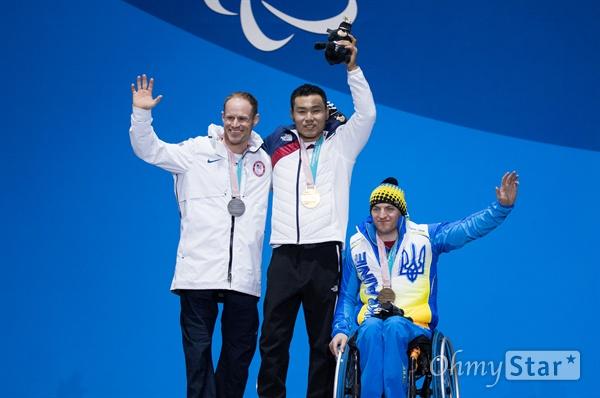 노르딕스키 신의현 선수가 17일 오후 강원도 평창 올림픽메달플라자에서 열린 크로스컨트리 남자 7.5km 좌식 부문 수상식에서 금메달을 받고 은메달을 받은 미국 다니엘 크노센, 동메달을 받은 우크라이나 막심 야로프이 선수와 함께 기념촬영을 하고 있다.