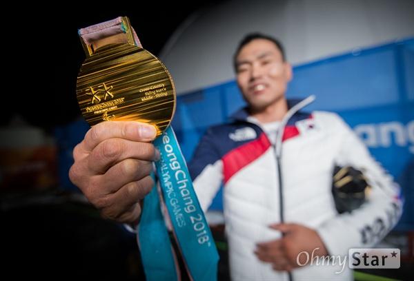 노르딕스키 신의현 선수가 17일 오후 강원도 평창 올림픽메달플라자에서 열린 크로스컨트리 남자 7.5km 좌식 부문 수상식에서 받은 금메달을 기자들에게 보여주고 있다.