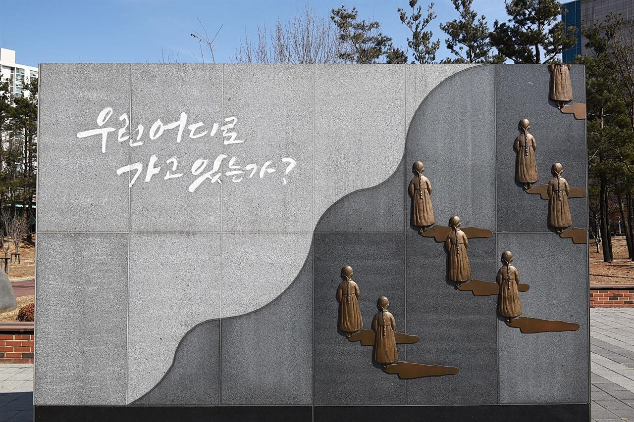 부천 평화의 소녀상 앞 벽 조형물  '우린 어디로 가고 있는가' 라는 글귀가 가장 먼저 눈에 들어온다. 그리고 똑같은 뒷모습이 소녀들이 우측 상단으로 끊임없이 확대 재생산된다.