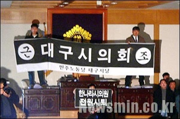 2005.12.26. 김성년 당시 민주노동당 대구시당 수성구당협 사무국장(현수막 든 오른쪽 사람)은 동료와 함께 대구시의회 본회의장 의장석을 박차고 올라 현수막을 펼쳐 들었다. (사진=김성년 제공)