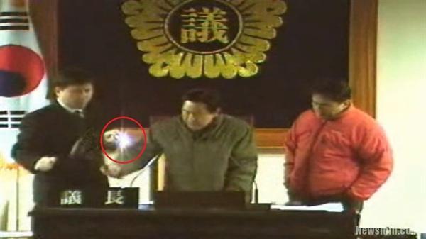 2005.12.24 당시 강황 대구시의회 의장(가운데)이 새벽 기습 쪼개기를 시도하고 있다. 강 의장 왼쪽으로 의회 직원이 손전등(붉은 원)으로 원고를 비추는 모습이 보인다. (사진=대구시의회 영상회의록 갈무리)