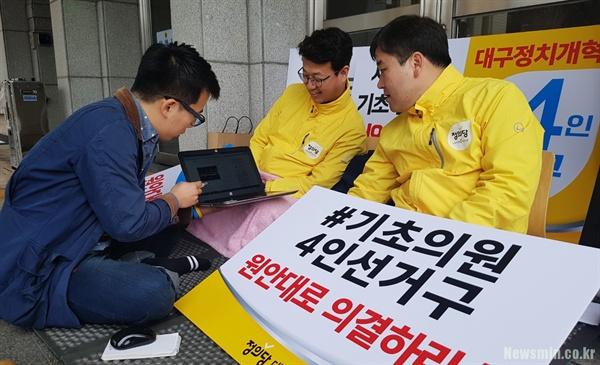 15일부터 단식 농성을 시작한 정의당 장태수(가운데) 서구의원과 김성년(가장 오른쪽) 수성구의원이 옛 기사를 함께 보면서 과거 기억을 이야기하고 있다.