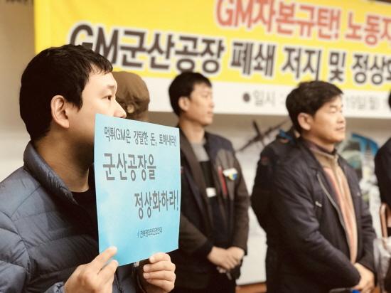 한국지엠 군산공장 폐쇄 저지 대책위 기자회견에 한 활동가가 피켓을 들고 있다.