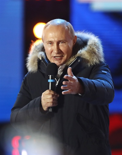 """푸틴, 대선 승리 확실시…출구조사 """"73% 이상 득표율"""" 블라디미르 푸틴 러시아 대통령이 18일(현지시간) 실시된 대선에서 압도적으로 승리한 것으로 출구조사 결과 나타나자 모스크바 크렘린궁 인근에서 열린 집회에서 지지자들에게 감사를 표시하고 있다. 현지 여론조사 기관들의 출구조사 결과 푸틴 대통령은 73% 이상의 득표율을 기록한 것으로 밝혀졌다."""