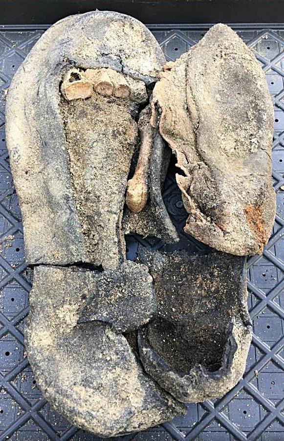 발굴 18일 째. 엄마의 왼발 신발에 담긴 발뼈와 아이의 고무신(오른 쪽)