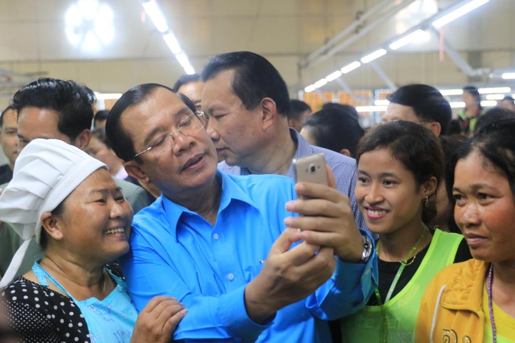 현지 봉제공장을 방문한 훈센 총리가 근로자들과 기념촬영을 하고 있다. 훈센 총리는 최근 미국 등 서방세계와 거리를 두는 대신 중국과 밀월관계를 유지하려고 애쓰고 있다.