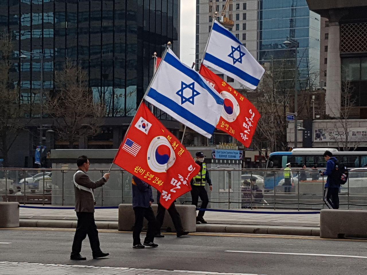 광화문광장 인근을 지나는 '애국보수집회' 집회 참가자들이 태극기와 성조기, 이스라엘국기가 그려진 깃발을 들며 행진하고 있다.