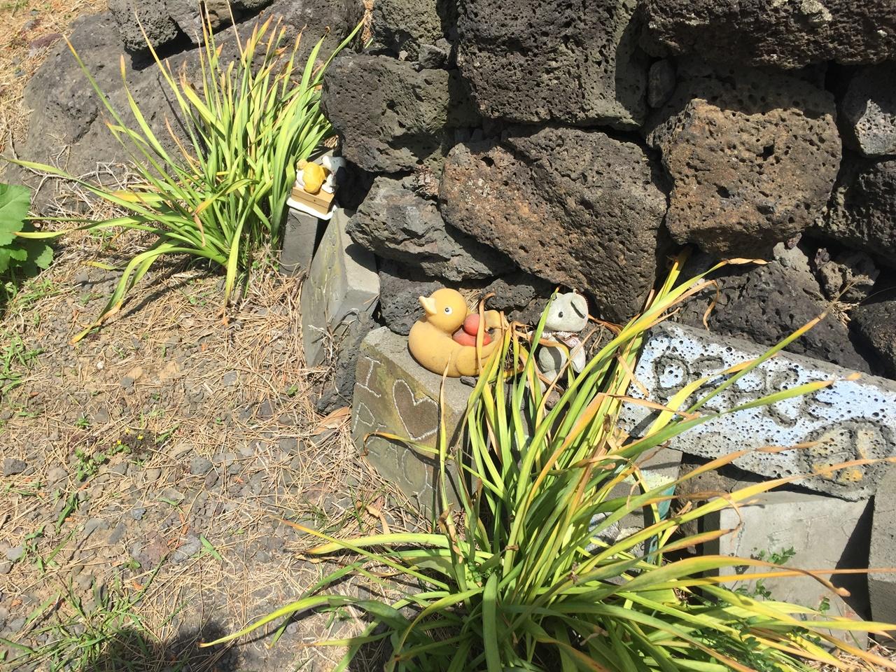 제주 너븐숭이의 아기무덤 장난감과 사탕이 있는