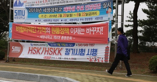 세명대 총학생회가 내건 원룸 가격 인하 촉구 현수막 앞으로 한 학생이 지나가고 있다.