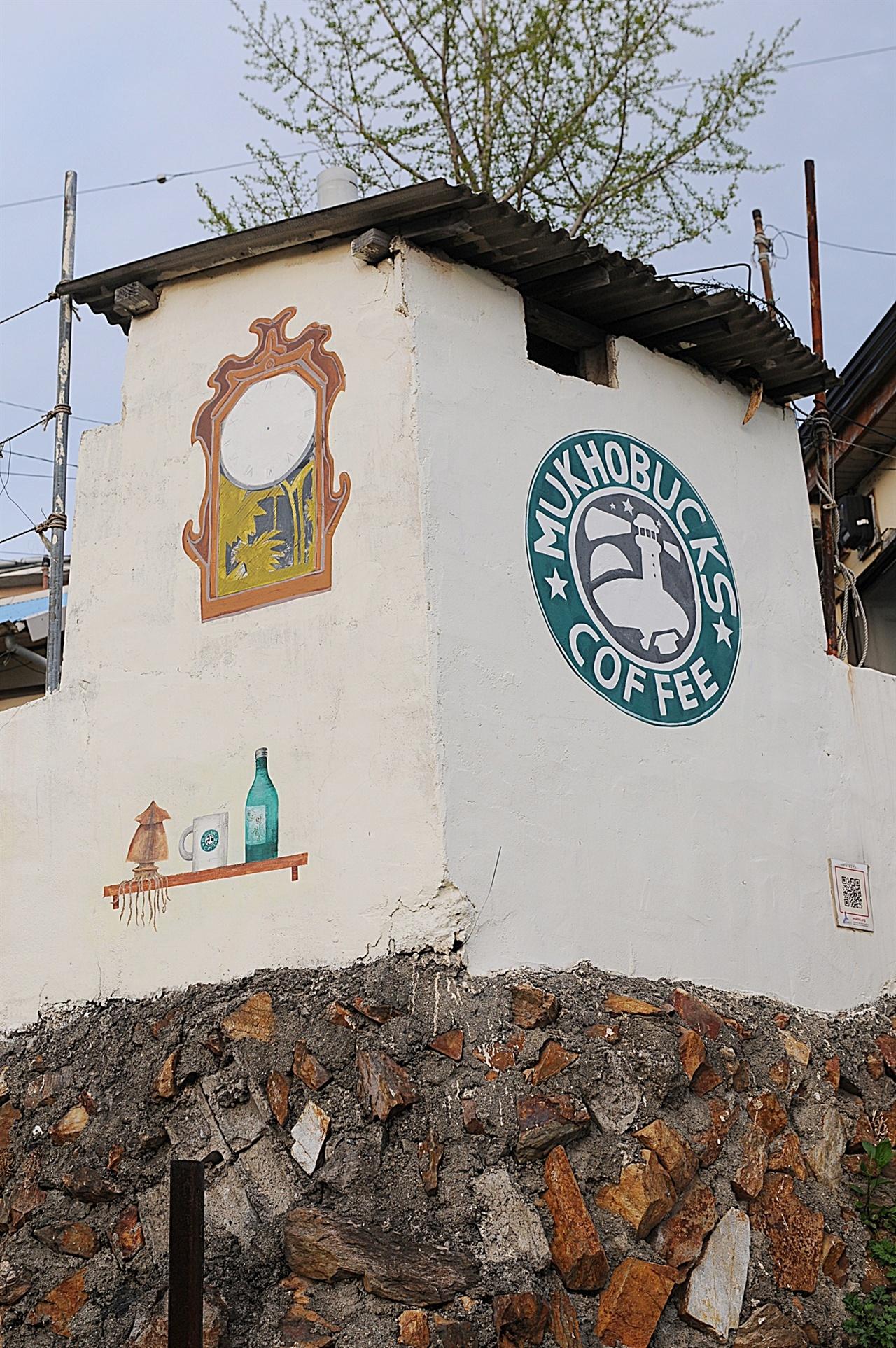 묵호벅스 벽화 스타벅스를 패러디한, 로열티를 내지 않는 순수 토종 브랜드 묵호벅스. 단, 매장이 없다. 그래도 소주와 오징어를 같이 먹도록 옆 벽에 그려 놓았다.