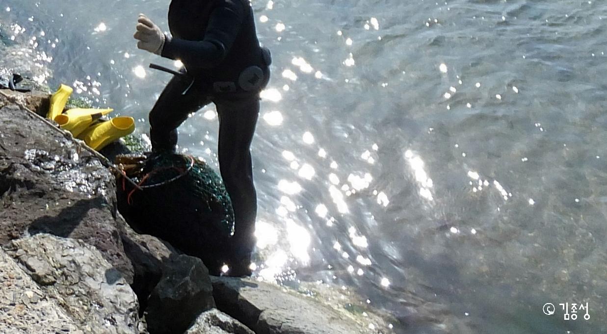 해녀의 허리춤에 있는 잠수용 납덩이와 작은 낫.