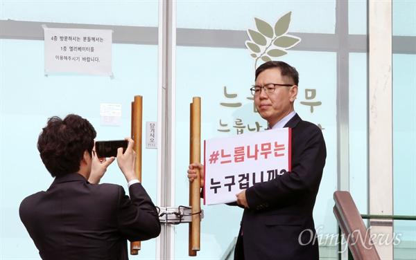 '#느릅나무는 누구겁니까' 인증샷 남기는 한국당 의원들 자유한국당 정태옥 의원이 24일 오전 경기 파주시 느릅나무 출판사 앞에서 비상의원총회를 마친 뒤 '#느릅나무는 누구겁니까'라고 적은 피켓을 들고 기념촬영을 하고 있다.