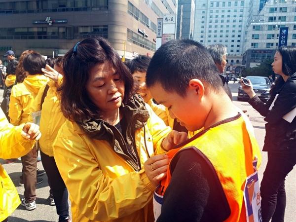 25일 세월호 가족들이 서울 여의도 자유한국당사 앞 기자회견을 마무리하는 도중, 참정권 요구 청소년들을 만나 노란 리본을 달아주며 응원의 뜻을 전하고 있다.
