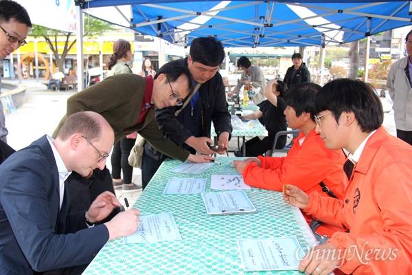 """시민들이 25일 오후 창원 상남동 분수광장에서 열린 """"남북정상회담 환영 문화제""""에서 '종전선언'에 서명하고 있다."""