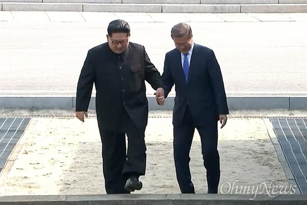 '2018남북정상회담'이 열리는 27일 오전 문재인 대통령과 김정은 국무위원장이 판문점에서 만났다. 문재인 대통령과 김정은 국무위원장이 손을 잡고 군사분계선을 넘고 있다.