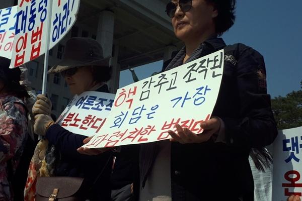 한 자유한국당 지지자가 29일 댓글조작 규탄 및 특검 촉구대회에 참석해 손팻말을 들고 있다.